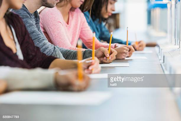 cropped view of group of teenagers taking a test - college application stock photos and pictures