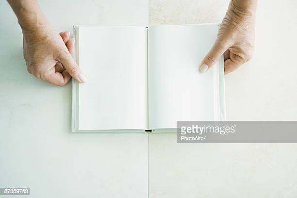 Cropped view of hands holding open book, viewed from directly above
