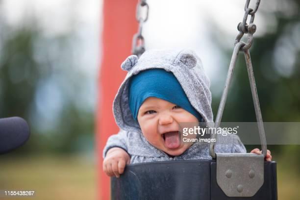 cropped view of happy baby on swing at park - actividad fotografías e imágenes de stock
