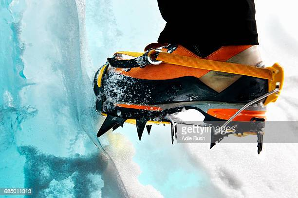 Cropped view of ice climbers feet wearing crampons