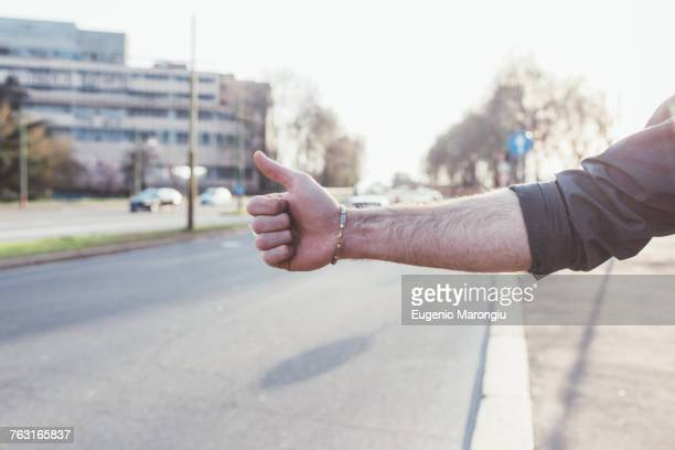 Cropped view of man hitchhiking