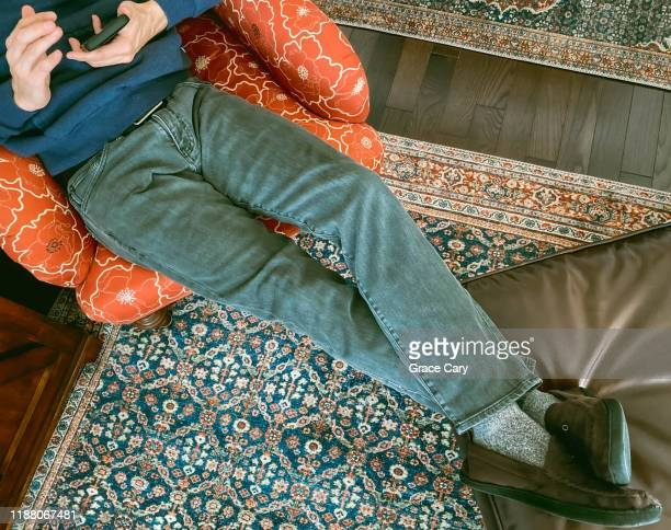 cropped view of man in arm chair looking at smart phone with feet on ottoman - ottomane stockfoto's en -beelden