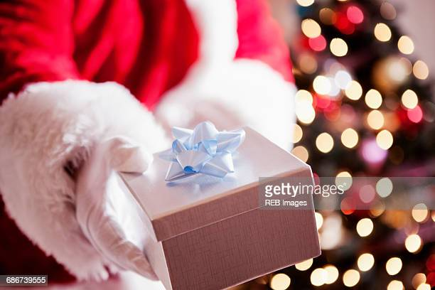 Cropped view of man in santa costume holding gift