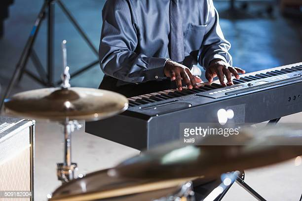 Cropped view of man playing keyboard in band