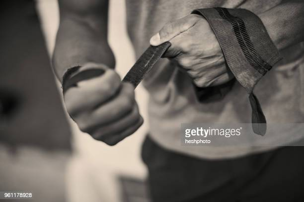 cropped view of man strapping hands with weightlifting straps - heshphoto fotografías e imágenes de stock