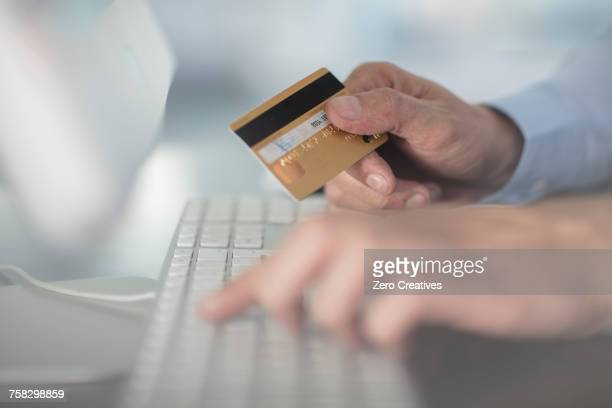 cropped view of man using keyboard holding credit card - input device stock photos and pictures