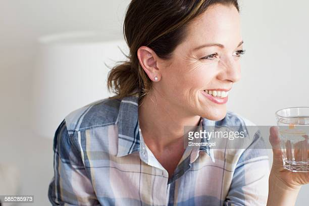 Cropped view of mature woman holding glass of water looking away smiling