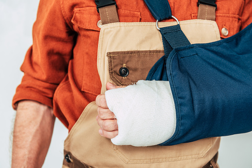 cropped view of repairman with broken arm and bandage on white background 1146110842