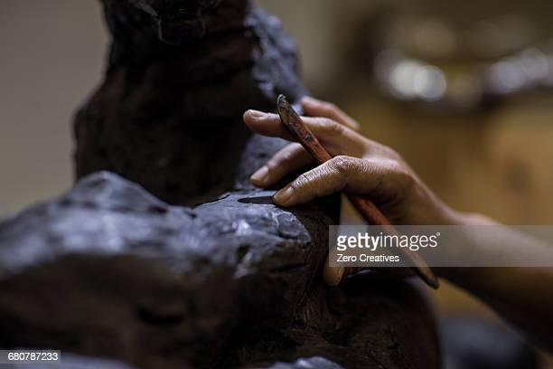 cropped view of sculptor in artists studio creating sculpture with hand tool - sculpture stock pictures, royalty-free photos & images