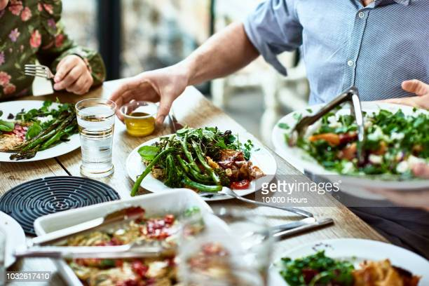 cropped view of table laid with crockery and fresh homemade vegetarian food - food stockfoto's en -beelden