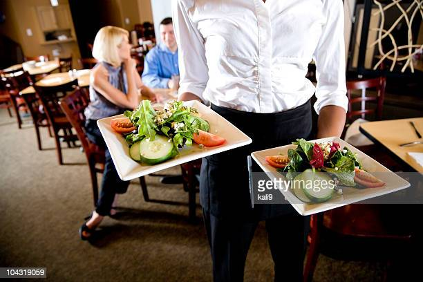 Cropped view of waitress holding salad plates in restaurant