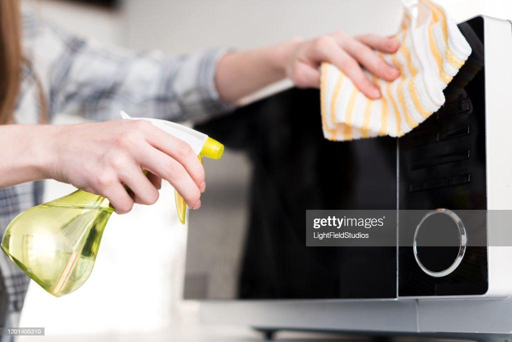 bijgesneden mening van vrouw die microgolf met vod in keuken schoonmaakt : Stockfoto