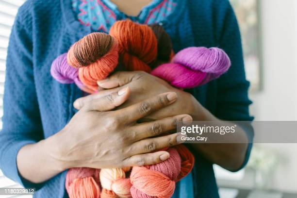 cropped view of woman clutching colorful yarn - knitting stock pictures, royalty-free photos & images