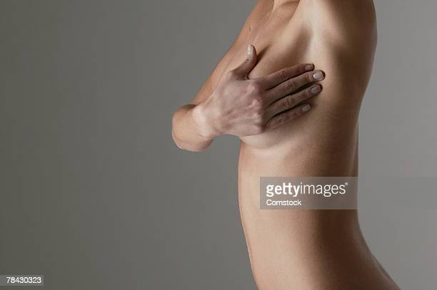 Cropped view of woman giving herself a breast exam