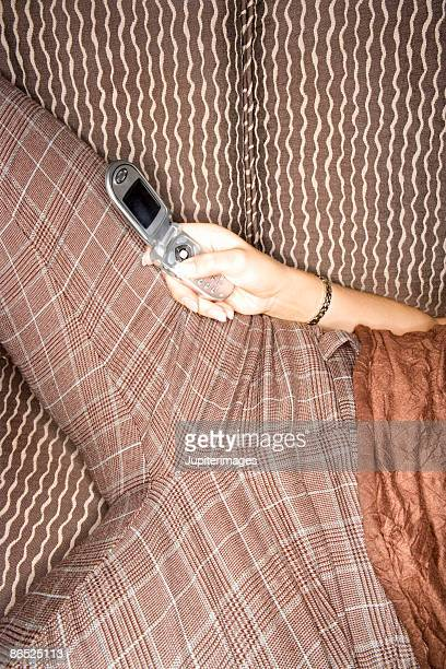 Cropped view of woman lying on couch text messaging