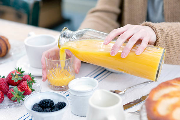 cropped view of woman pouring orange juice from bottle into glass - fruit juices stock pictures, royalty-free photos & images