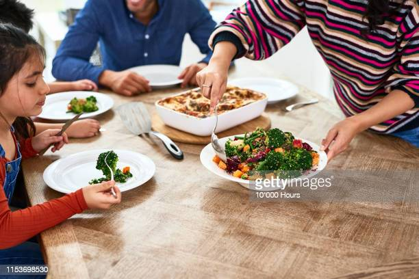 cropped view of woman serving vegetables to family - healthy eating stock pictures, royalty-free photos & images