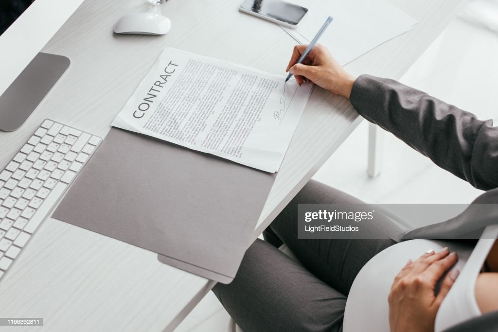 cropped view of woman signing document while sitting in office : Stock Photo