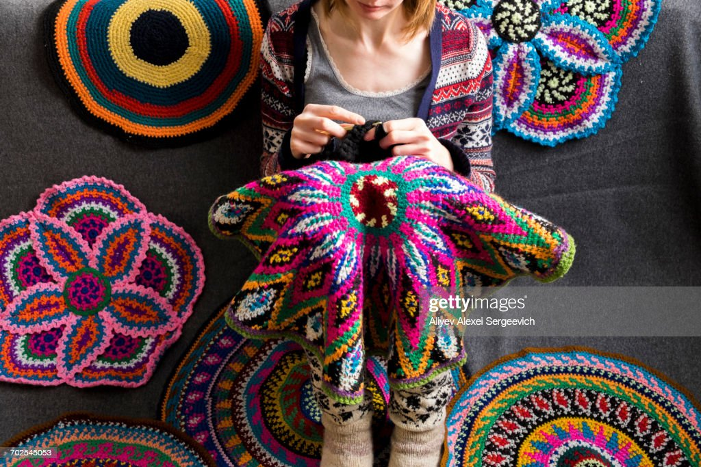 Cropped view of woman sitting on floor crocheting, surrounded by crochet circles : Stock Photo