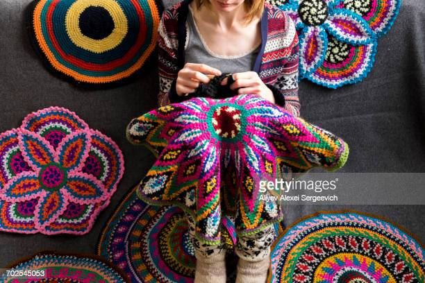 Cropped view of woman sitting on floor crocheting, surrounded by crochet circles