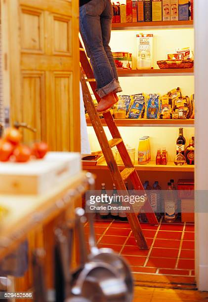 Cropped view of woman standing on ladder in pantry