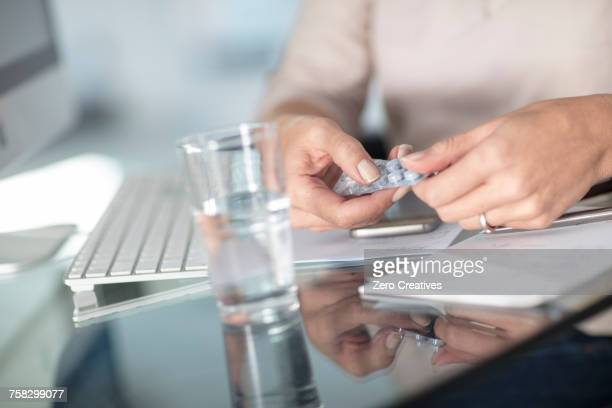 Cropped view of woman taking pills