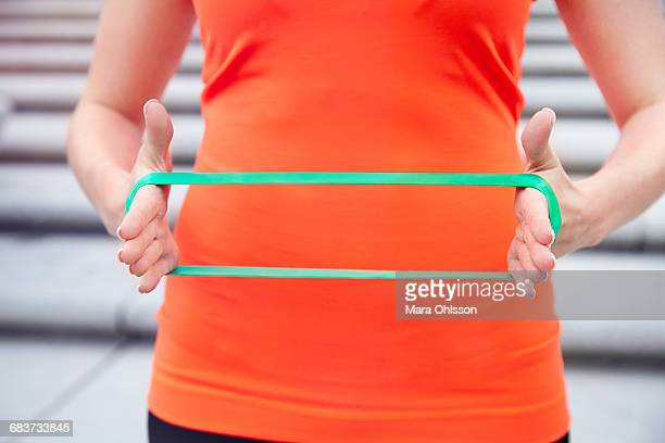 Cropped view of woman using resistance band