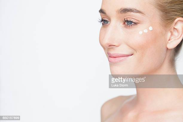 Cropped view of woman with face cream on cheek looking away smiling
