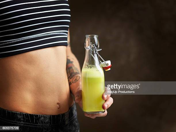 Cropped view of womans bare midriff, holding raw juice in glass bottle