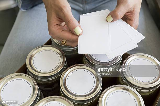 cropped view of womans hands labelling jars - labeling stock photos and pictures