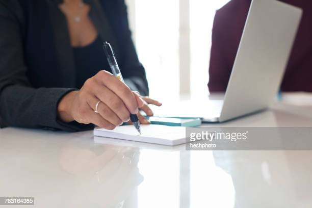 cropped view of young businesswoman making notes at office desk - heshphoto fotografías e imágenes de stock