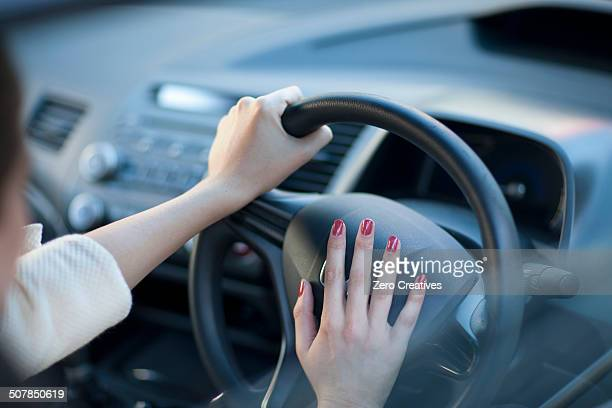 Cropped view of young businesswoman's hands pressing car horn