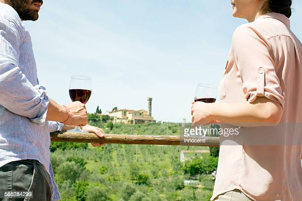 cropped view of young couple face to face holding wine glasses - chianti region stock photos and pictures