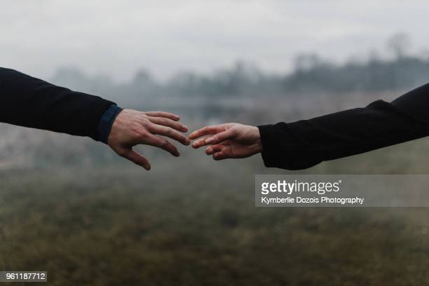 cropped view of young couple holding hands, fingers touching - reaching stock pictures, royalty-free photos & images