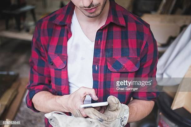 cropped view of young mans hands wearing protective gloves using smartphone - world at your fingertips stock pictures, royalty-free photos & images