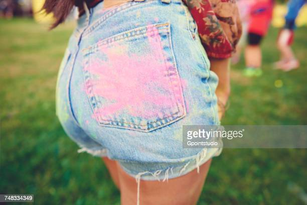 Cropped view of young womans denim shorts with pink chalk handprint on buttock at festival