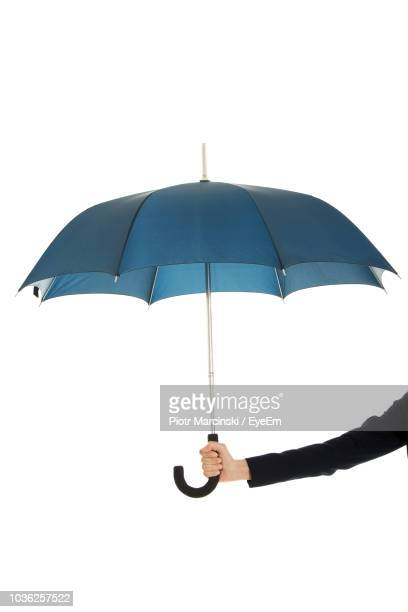 cropped woman hand holding umbrella against white background - umbrella stock pictures, royalty-free photos & images