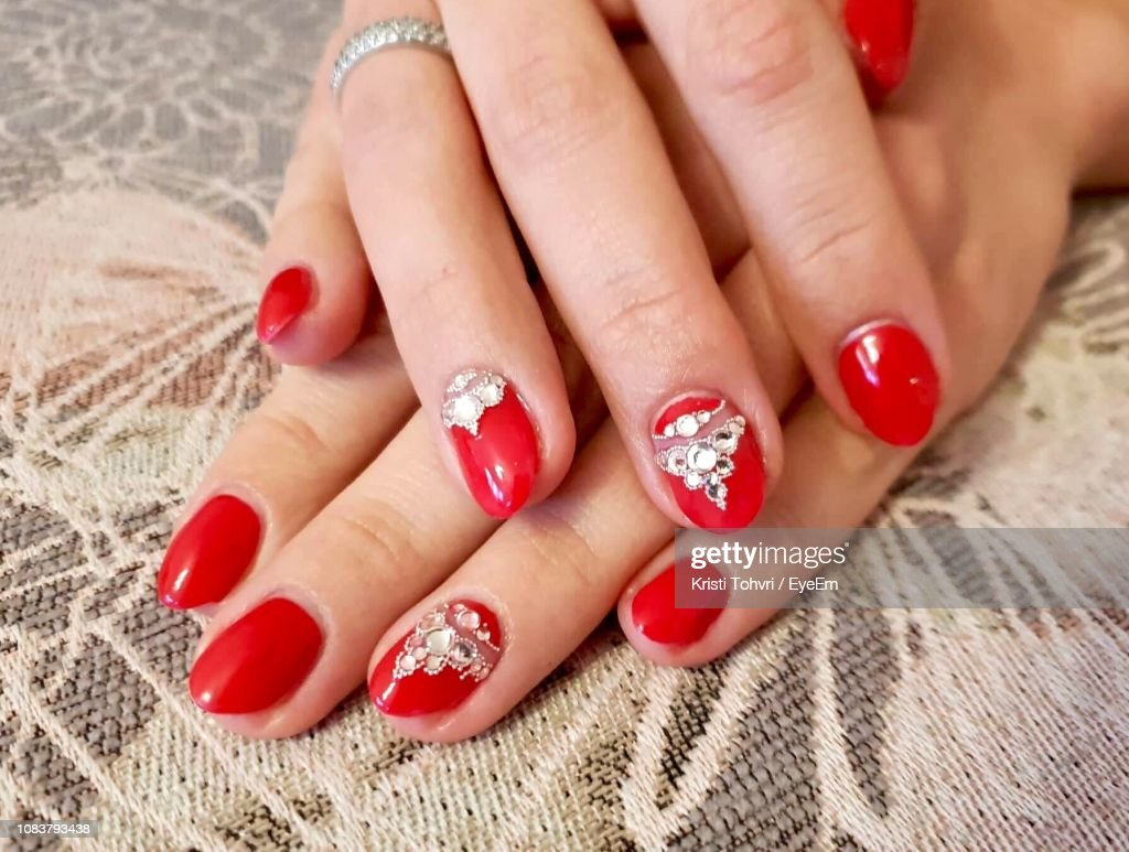 Cropped Woman Hands With Red Nail Polishes On Seat : Stock Photo