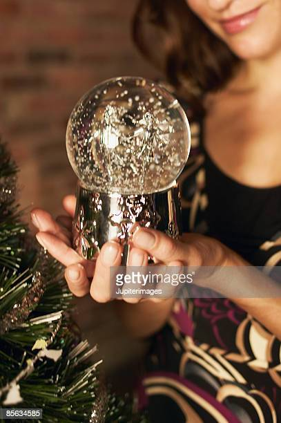 Cropped woman holding snowglobe