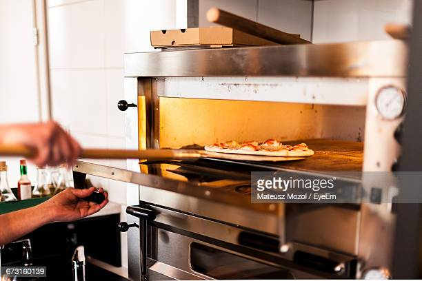 cropped woman putting pizza in oven - pizza oven stock photos and pictures