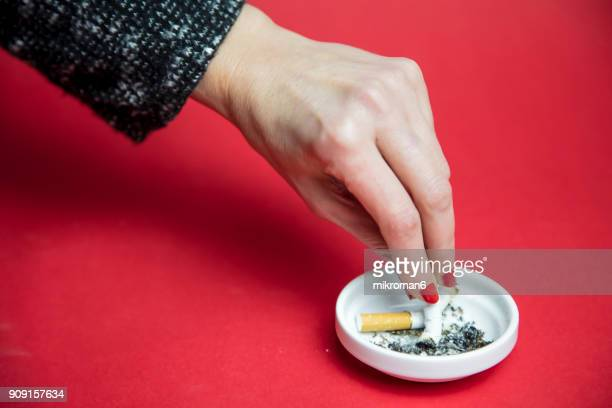 Cropped Woman's Hand Extinguishing Cigarette In Ash Tray