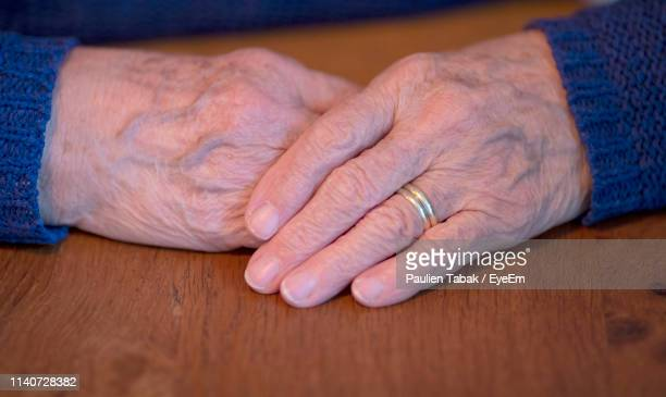 cropped wrinkled hands of person on wooden table - paulien tabak stock pictures, royalty-free photos & images