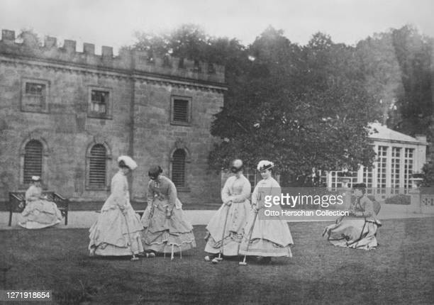 A croquet party a group of women in Victorian fashions all wearing bellshaped skirts on the lawn at Goodwood House in Westhampnett Chichester West...