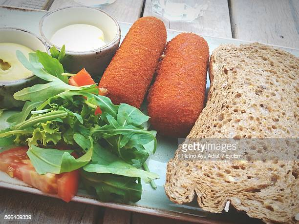 Croquette And Bread Served With Salad On Plate
