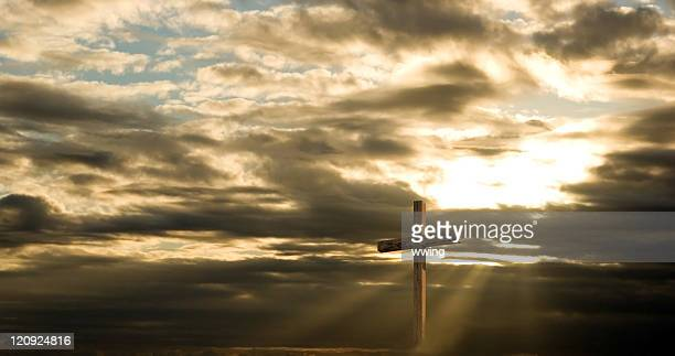 cross and dramatic sky with sun rays and dark clouds - death and resurrection of jesus stock photos and pictures