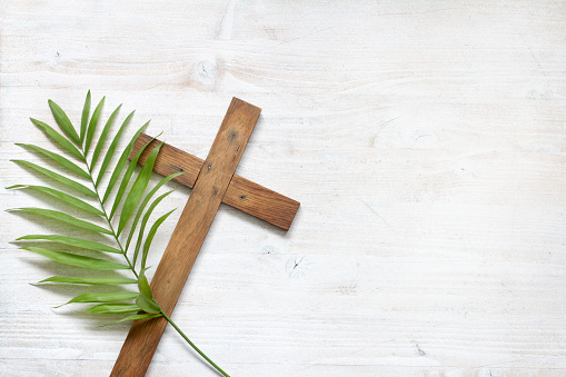 Cross and palm on wooden white background easter sign symbol concept 1129579339