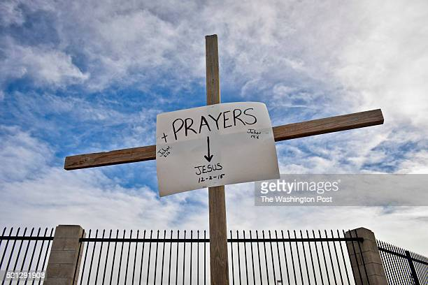 Cross and sign erected by Manny Guzman on the southeast corner of Waterman and Orange Show Ln Thursday afternoon. Guzman's father was shot and killed...