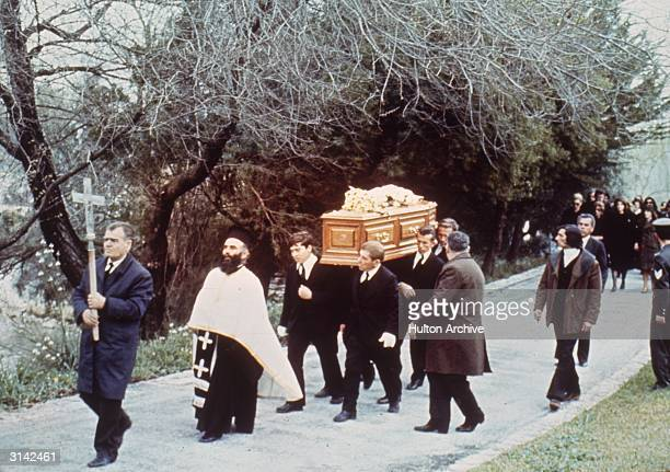 A cross bearer and a priest precede the coffin of Greek shipping tycoon Aristotle Onassis during his funeral procession on the Ionian island of...