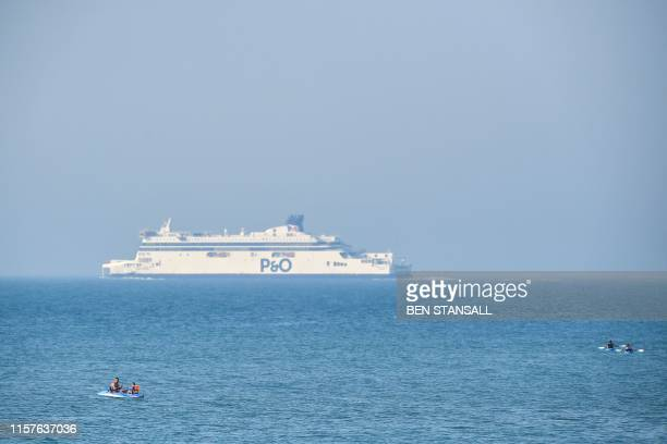 A PO cross channel ferry starts it's voyage as people float in rubber dingeys close to the White Cliffs of Dover on the southeast coast of England on...