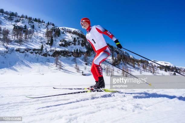 クロスカントリー選手のスケートは、晴れた日に山で雪トラックをスポーツします。